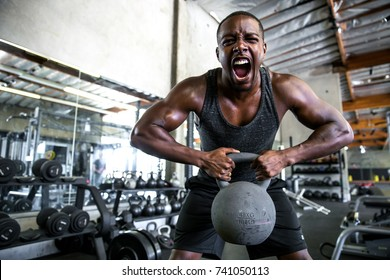 Man shouts and screams pushing hard with dedication and determination lifting heavy kettlebell