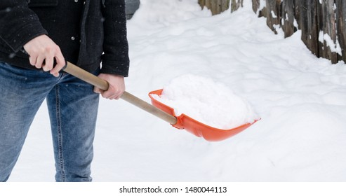 Man with shovel cleaning back yard from snow.