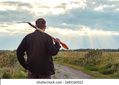 a man with a shovel on his shoulder stands with his back looking into the distance on a field road above him a cloudy sky. in search of a place where you can dig a grave for a pet