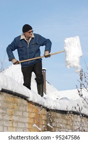A man with a shovel removing snow from a roof . Near Kiev,Ukraine
