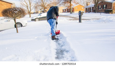 Man shoveling his sidewalk to his car winter 2019 Kentucky Urban photography