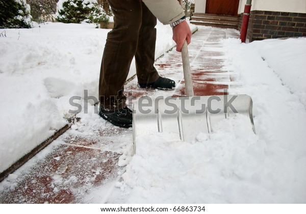 Man shoveling snow at a footpath