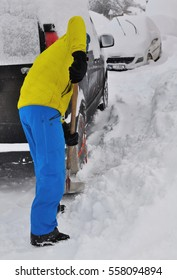 man shoveling the snow in front a car