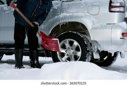 Man shoveling snow from his car