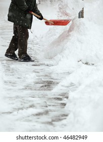 Man shoveling snow from the sidewalk in front of his house after a heavy snowfall in a city