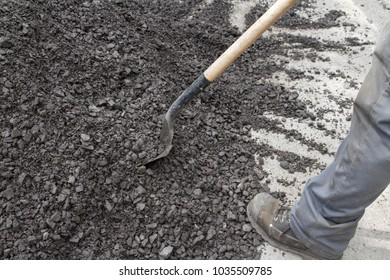 man shovelling rocky gravel on a summer day outdoor