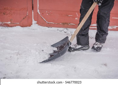 The man shovels away snow in the winter outside