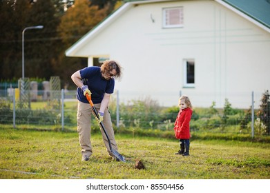 A man shovels a hole in the yard, preparing to plant a tree