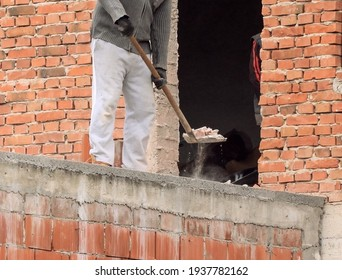 A man shovels removes debris of a drilled hole in the wall
