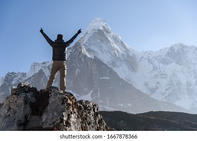 A man show up his hands and face against Ama dablam mt.