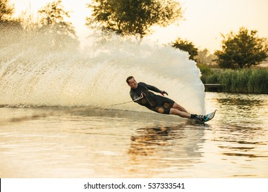 Man show of his water skiing skill on a lake. Athlete doing stunts on wakeboard.
