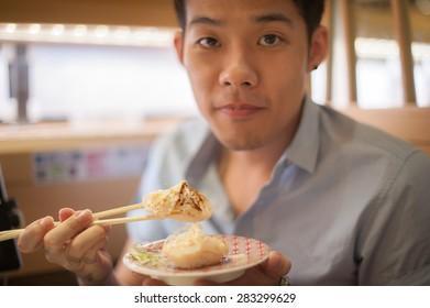 Man show the scallops sushi