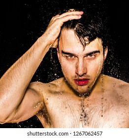 Man in the shower with hand in his hair and drops of water falling around his skin. We can see his hand, face, shoulders, clavicle and arm.