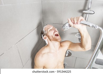 A man in shower washing his hair with shampoo