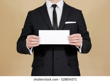 Man showing blank black flyer brochure booklet. Leaflet presentation. Pamphlet hold hands. Man show clear offset paper. Sheet template. Man in a black suit, white shirt and tie