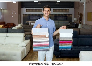 Man is showing colors for sofas in furnishings store