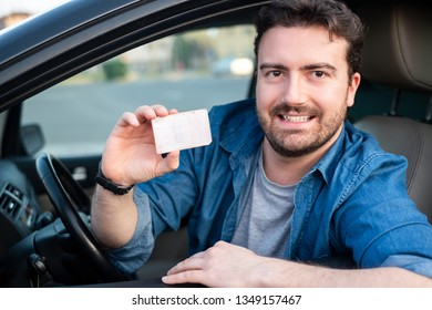 Man showing driving license seated in car