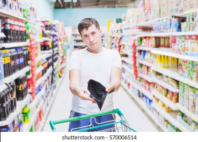 man showing empty wallet in supermarket, no money to buy, expensive food shopping