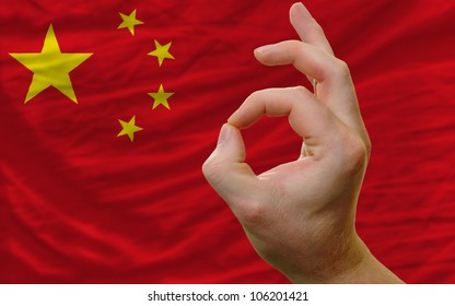 man showing excellence or ok gesture in front of complete wavy china national flag of  symbolizing best quality, positivity and success