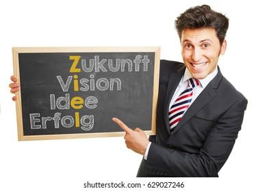 "Man showing German concept ""Zukunft Vision Idee Erfolg Ziel"" (future vision idea success goal) on a blackboard"