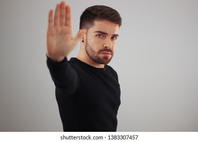 man showing hand and palm lines forward with body - young man demonstrating strength of hands - concept of stop, strength, hands and dna - five fingers in the hand - blurred hand