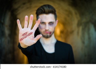 "Man showing hand with text ""stop homophobia"""