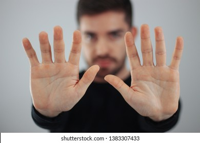 man showing hands and palm lines forward with blurred body - young man demonstrating strength of hands - concept of stop, strength, hands and dna - ten fingers in the hand