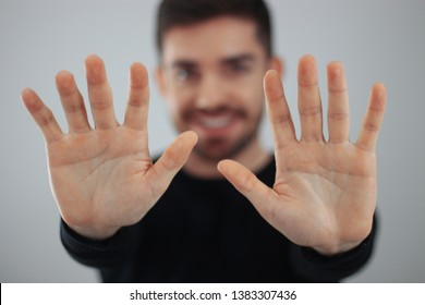 man showing hands and palm lines forward with blurred body - young man demonstrating strength of hands - concept of stop, strength, hands and dna - ten fingers in the hand - smiling