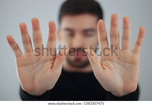 man showing hands and palm lines forward with blurred body - young man demonstrating strength of hands - concept of stop, strength, hands and dna - ten fingers in the hand - closed eyes