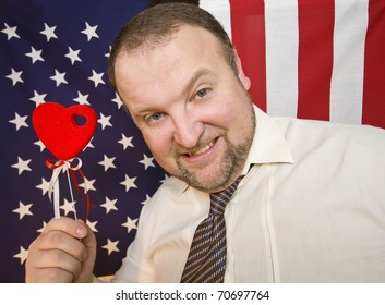 Man is showing heart sign against the background of the flag of America