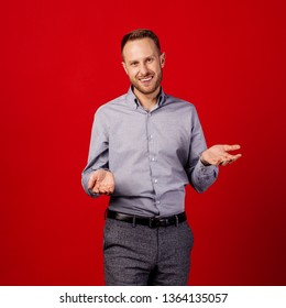 man showing helpless gesture with arm and hands over red background. people and emotion concept.