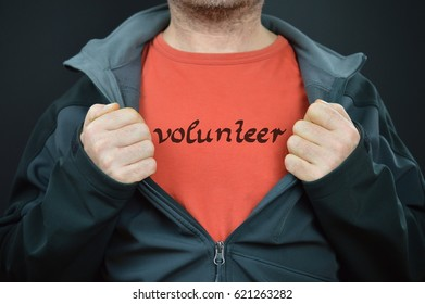 man showing his t-shirt with the word VOLUNTEER written on it