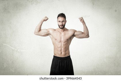 man showing muscles in abstract room. textured wall