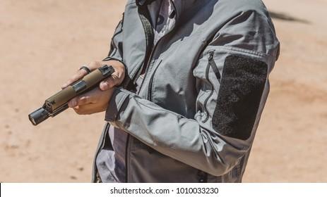 Man showing pistol in desert range close up