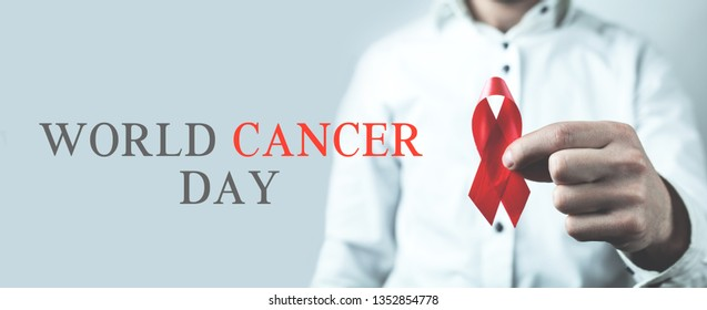 Man showing red ribbon. World Cancer Day