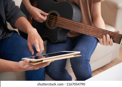Man showing sheet music on tablet computer to his girlfriend who is playing guitar