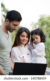 man showing something on the laptop to wife and daughter.