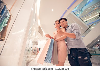 Man showing something in the shop window to his wife
