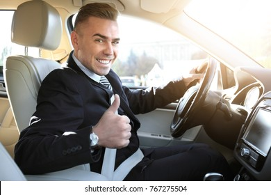 Man showing thumb up gesture when sitting on driver's seat of car