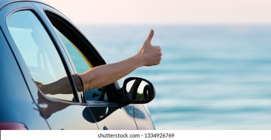 Man showing thumbs up from car window with sunset sky and blue sea at background. Copy space on right side. Traveling by car or rent car concept