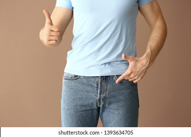 Man showing thumb-up on color background. Urology concept
