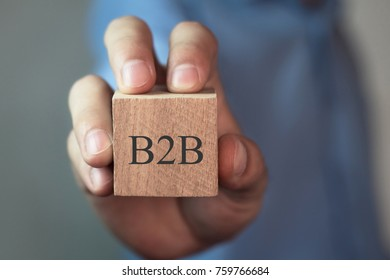 Man showing wooden cube with a written B2B word.
