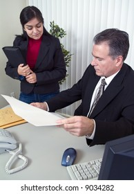 A man showing a young woman something that appears to be a legal document.