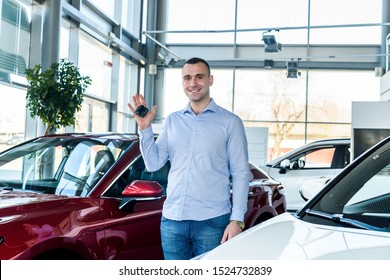 Man in showroom holding keys from new car