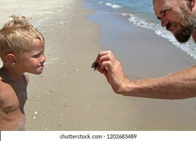 A man shows a child caught a crab fear