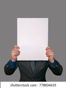 A man shows an empty white large A3 A2 paper, covering his face. Presentation of leaflets. Leaf pattern. The face of the sheet is read. Template for writing on a sheet