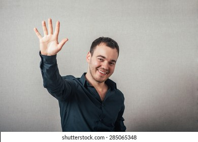 A man shows his hand hello. On a gray background.