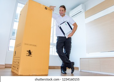 A man shows a large package in an empty room. The postman delivers the parcel to the new apartment.