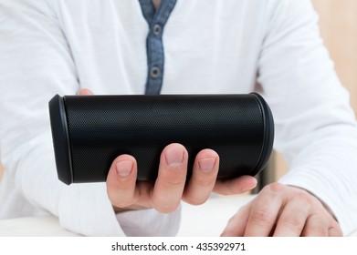 Man shows Modern wireless audio device.