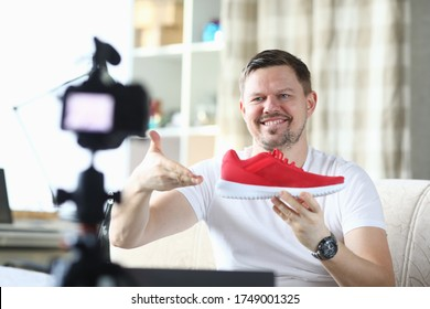 Man shows red sneaker in front camera, video blog. Quality product description. Guy works remotely, offering goods online. Man in his apartment takes an overview new sports shoes